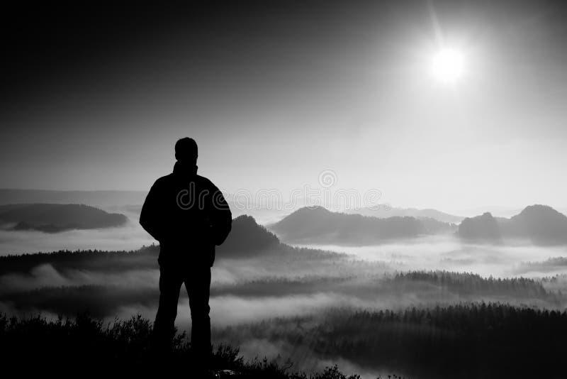 Bello momento il miracolo della natura L'uomo sta sul picco della roccia dell'arenaria in parco nazionale Sassonia Svizzera e gua immagini stock libere da diritti