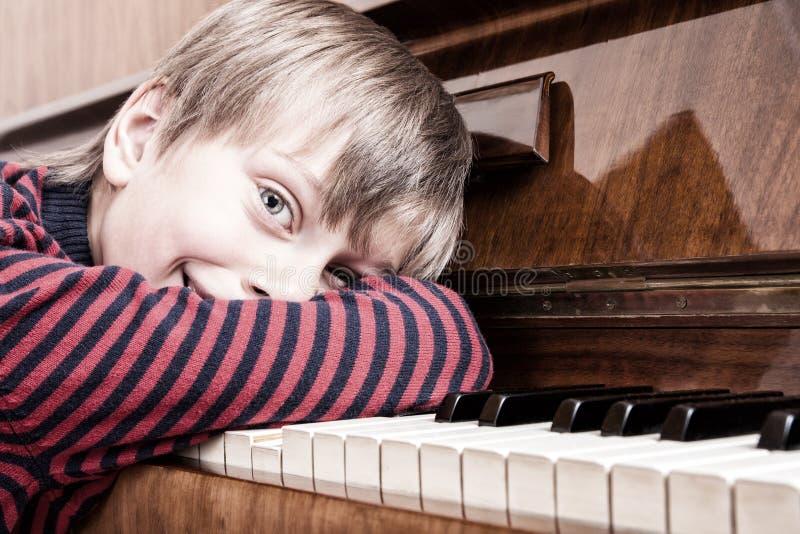 Bello musicista divertente del bambino che gioca sorridere del piano fotografia stock