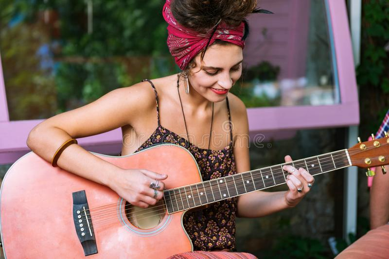 Bello musicista femminile che gioca sulla chitarra che si siede in caffè fotografia stock