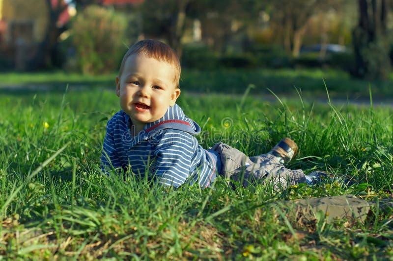Bello neonato che si trova sull'erba verde fotografia stock libera da diritti
