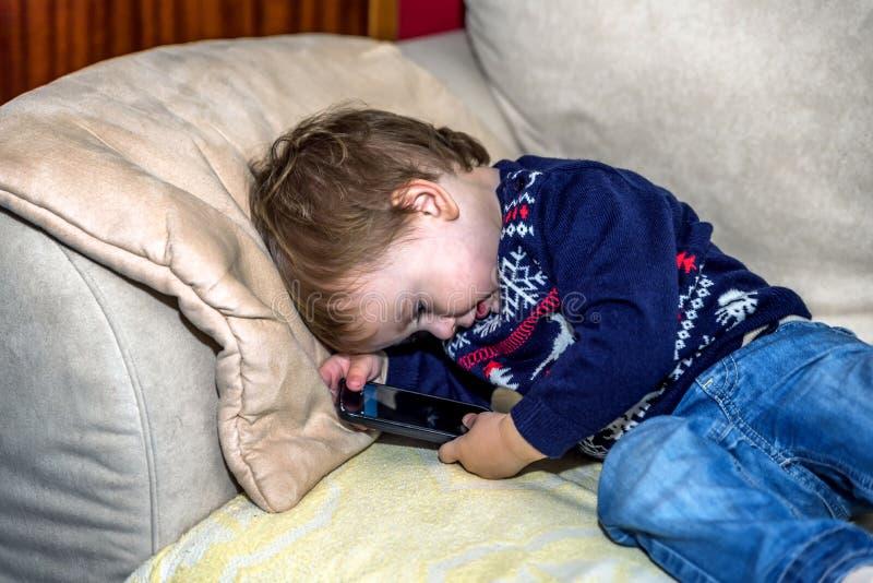 Bello neonato in un saltatore di natale che si trova sullo strato nel salone e che gioca con lo smartphone immagine stock libera da diritti
