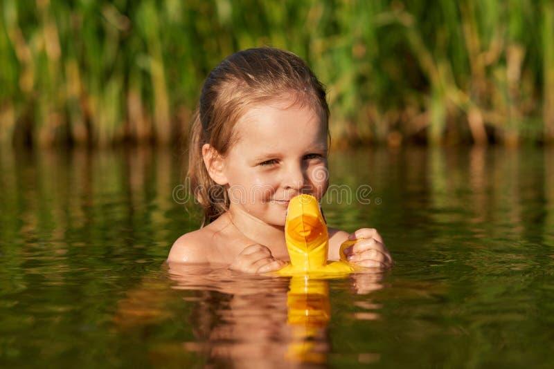 Bello nuoto positivo del bambino nel lago locale da solo, tenendo la sua anatra di gomma per acqua, godendo delle vacanze estive, immagini stock libere da diritti