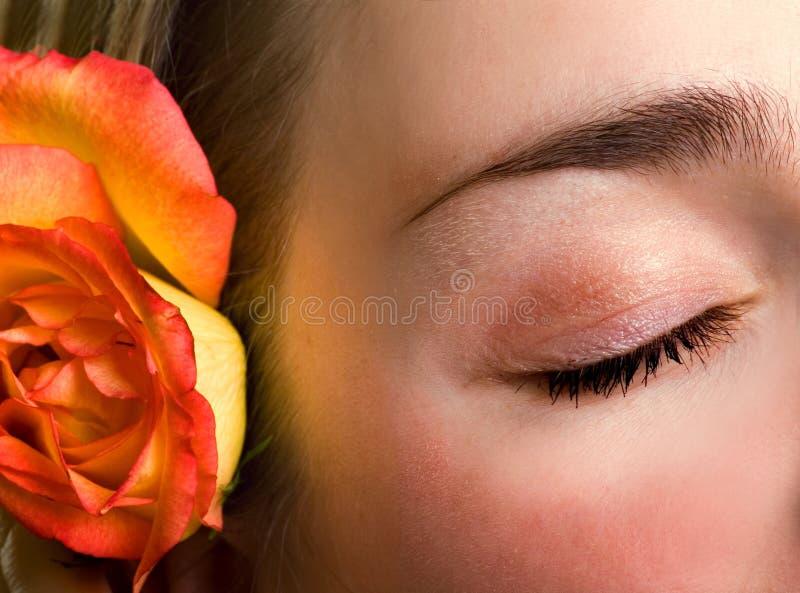 Bello occhio chiuso femminile e primo piano di rosa immagine stock