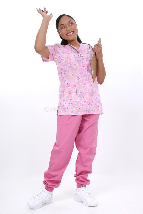 Bello ondeggiamento pediatrico sorridente dell'infermiera fotografia stock