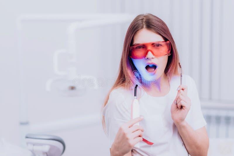 Bello ortodontista della ragazza che posa con gli strumenti in clinica immagine stock libera da diritti