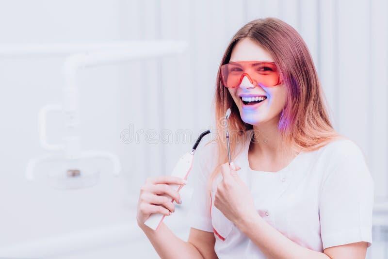 Bello ortodontista della ragazza che posa con gli strumenti in clinica fotografia stock