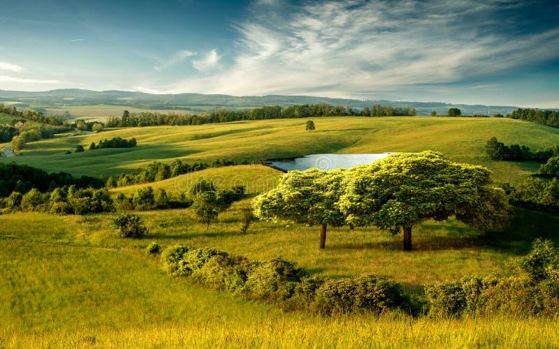 Bello paesaggio collinoso con il lago ed il cielo nuvoloso blu fotografia stock