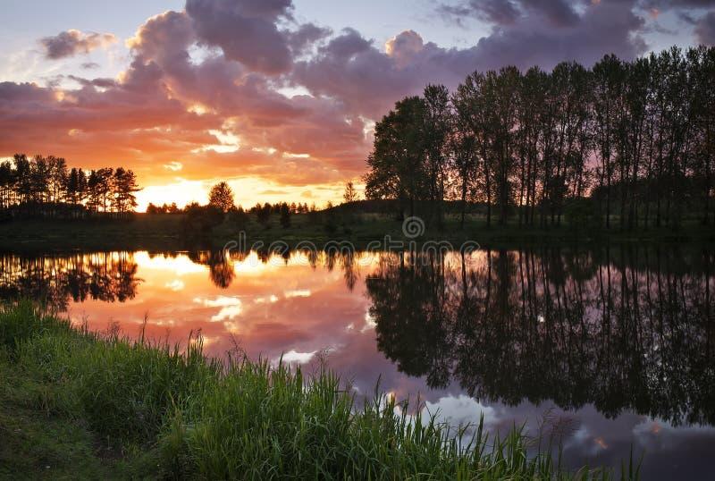 Bello paesaggio con il tramonto ardente sopra il lago immagine stock