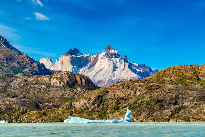 Bello paesaggio con l'iceberg che galleggia nel lago grigio davanti alla bella montagna immagini stock