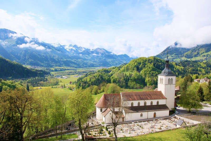 Bello paesaggio con la chiesa in Gruyeres, Svizzera Montagne delle alpi e campi, giorno di estate grazioso fotografie stock