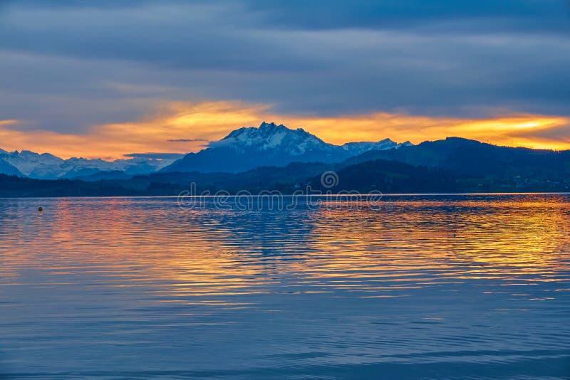 Bello paesaggio con un lago circondato dalle alte montagne e da un cielo nuvoloso al tramonto, Svizzera, lago Zugo fotografia stock