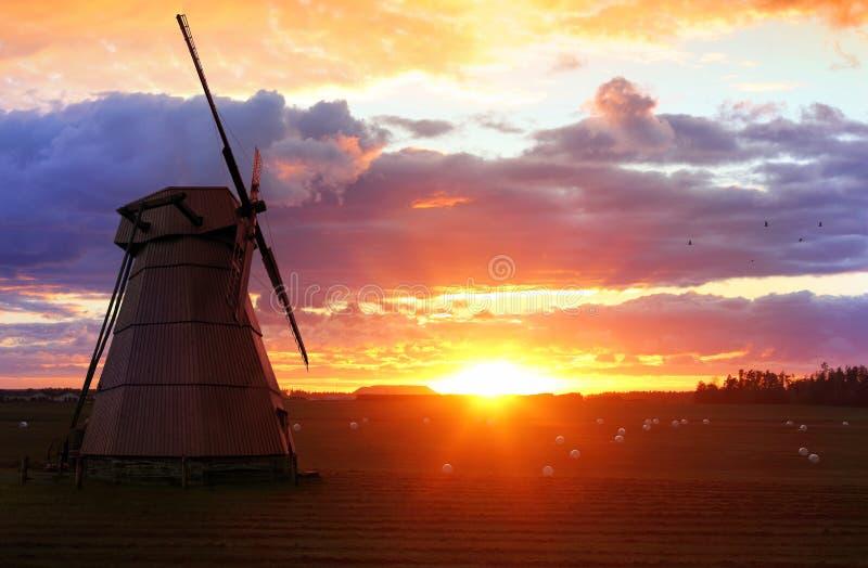 Bello paesaggio con un mulino a vento al tramonto fotografia stock libera da diritti