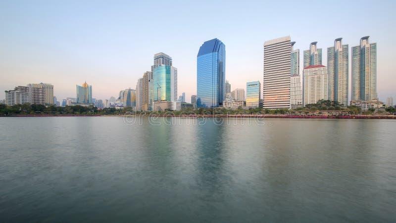 Bello paesaggio dei grattacieli della riva del lago che riflettono sull'acqua liscia del lago nel parco di Benjakiti, Bangkok Tai fotografie stock libere da diritti