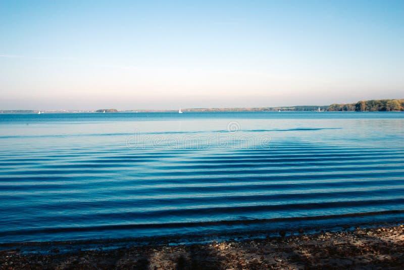 Bello paesaggio del lago e tramonto Onde e linea blu di orizzonte su acqua Bello fondo fotografia stock