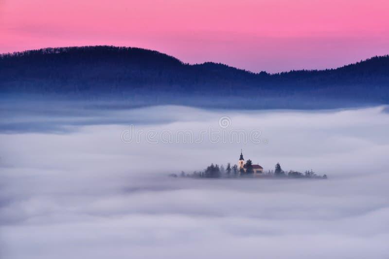 Bello paesaggio della Slovenia con foschia e la chiesa di mattina immagini stock libere da diritti