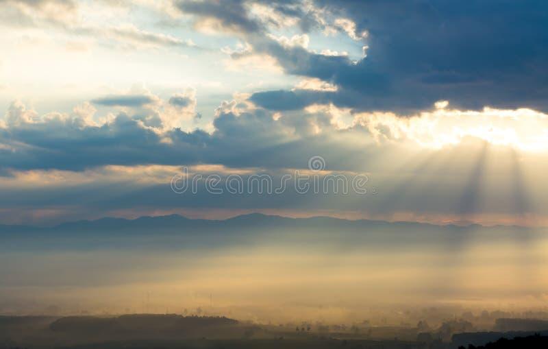 Bello paesaggio di alba con illuminazione del sole e della foschia fotografia stock