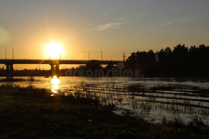 Bello paesaggio di autunno con un ponte nei raggi arancio del tramonto in Europa immagine stock libera da diritti