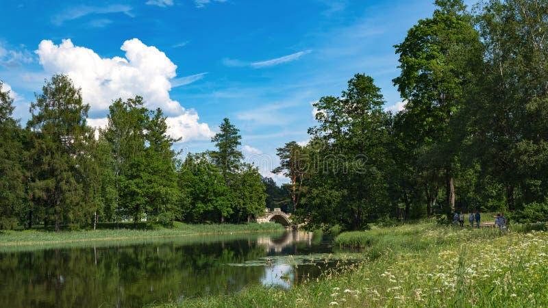Bello paesaggio di estate con un vecchio ponte sopra lo stagno nel parco immagini stock