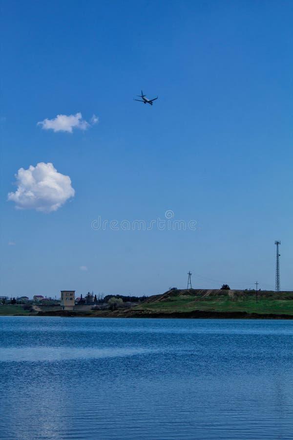 Bello paesaggio Il lago, le montagne e l'aereo vola nel cielo con le nuvole Cielo blu fotografia stock