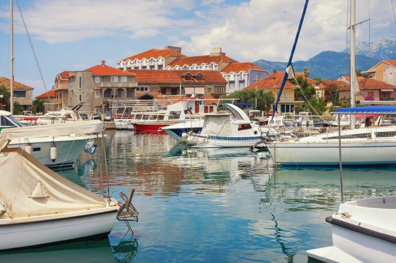 Bello paesaggio mediterraneo Città della spiaggia: case con i tetti rossi ed i pescherecci in porto Il Montenegro, città di Teodo fotografia stock libera da diritti