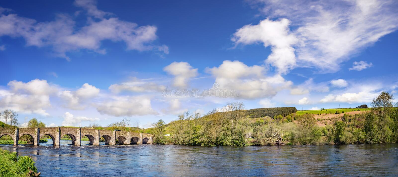 Bello paesaggio panoramico con un vecchio ponte di pietra su un sunn immagine stock libera da diritti