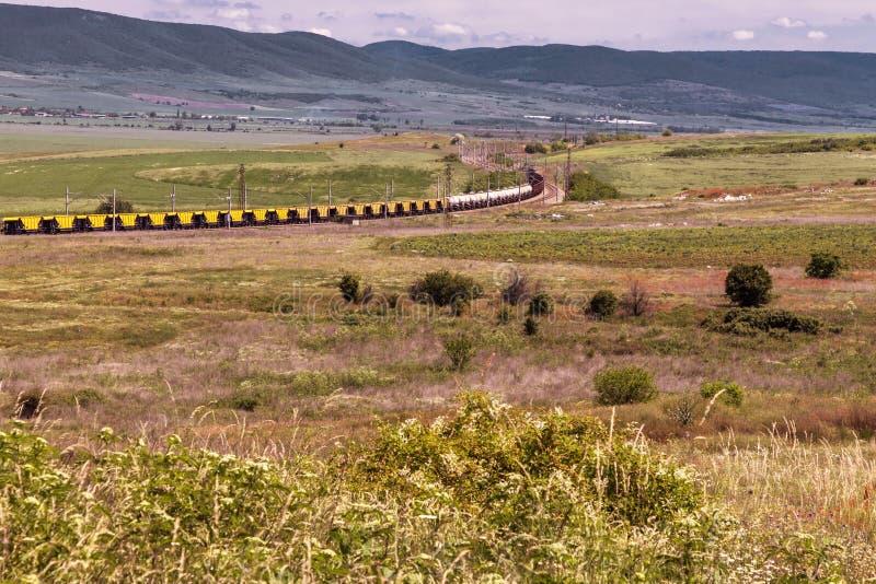 Bello paesaggio, treno ferroviario attraverso il campo verde, alte montagne immagini stock