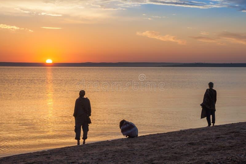 Bello paesaggio variopinto di alba del mare di estate con un cielo blu E ricerca irriconoscibile delle siluette della gente fotografie stock