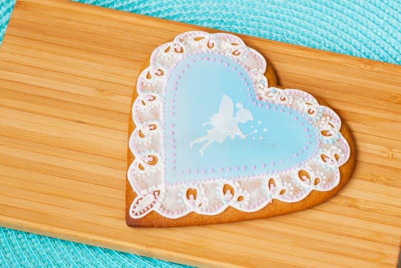Bello pan di zenzero blu pastello con un modello openwork e l'immagine di piccolo fatato sveglio, fondo di legno immagini stock