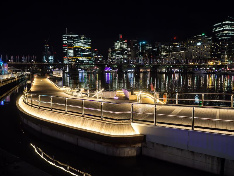 Bello passaggio pedonale di harbourside di lungomare a Darling Harbour con la vista di paesaggio urbano ai precedenti nella notte immagine stock