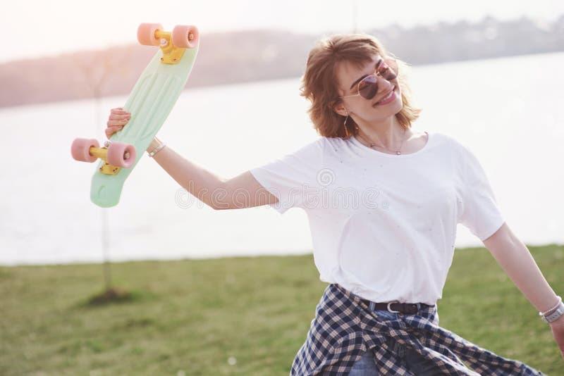 Bello pattinatore femminile teenager che si siede sulla rampa al parco del pattino Concetto delle attività urbane di estate immagini stock