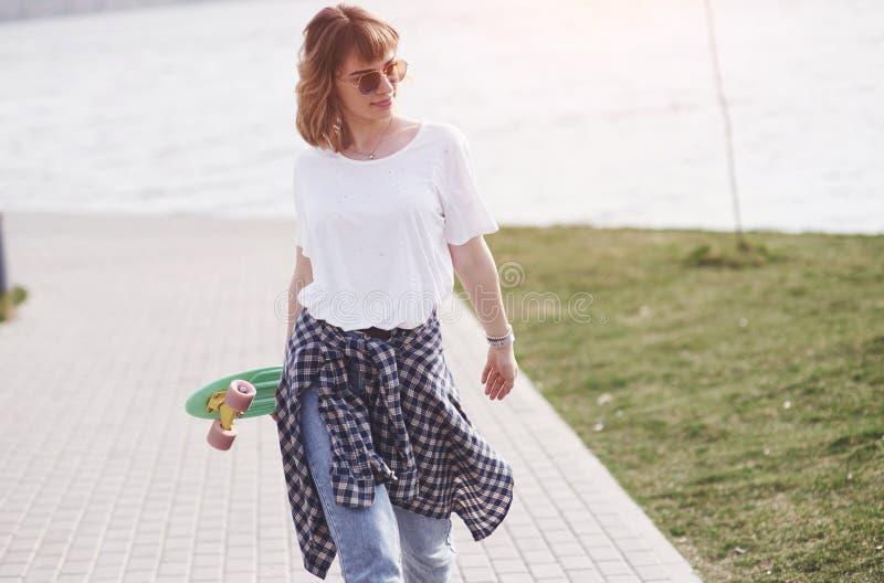 Bello pattinatore femminile teenager che si siede sulla rampa al parco del pattino Concetto delle attività urbane di estate immagine stock