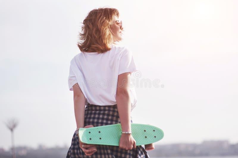 Bello pattinatore femminile teenager che si siede sulla rampa al parco del pattino Concetto delle attività urbane di estate fotografie stock libere da diritti