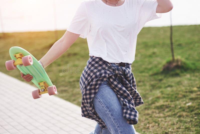 Bello pattinatore femminile teenager che si siede sulla rampa al parco del pattino Concetto delle attività urbane di estate fotografia stock