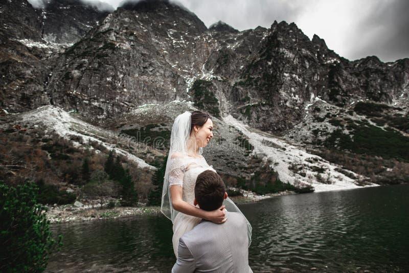 Bello photosession di nozze Lo sposo circonda la sua giovane sposa, sulla riva del lago Morskie Oko poland fotografia stock