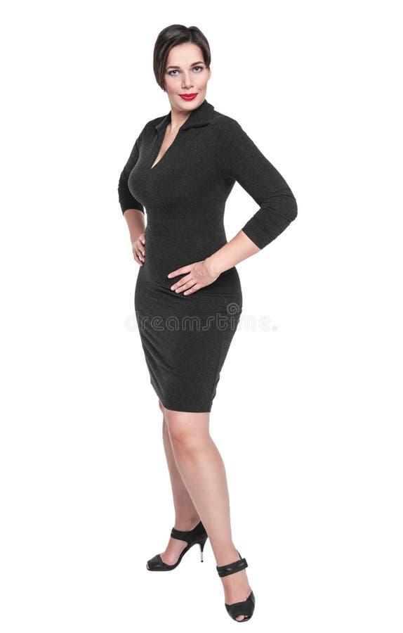 Bello più la donna di dimensione nella posa nera del vestito isolata fotografia stock