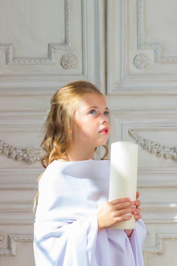 Bello piccolo angelo con pregare della candela immagine stock
