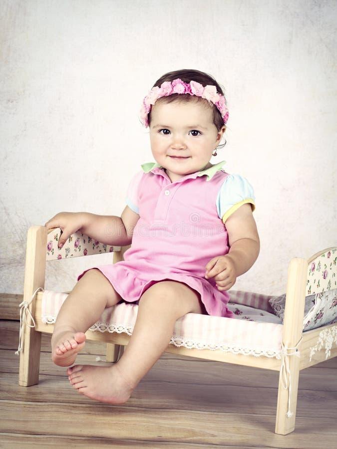 Bello piccolo bambino con la fascia floreale che si siede sul letto e sul sorridere immagini stock