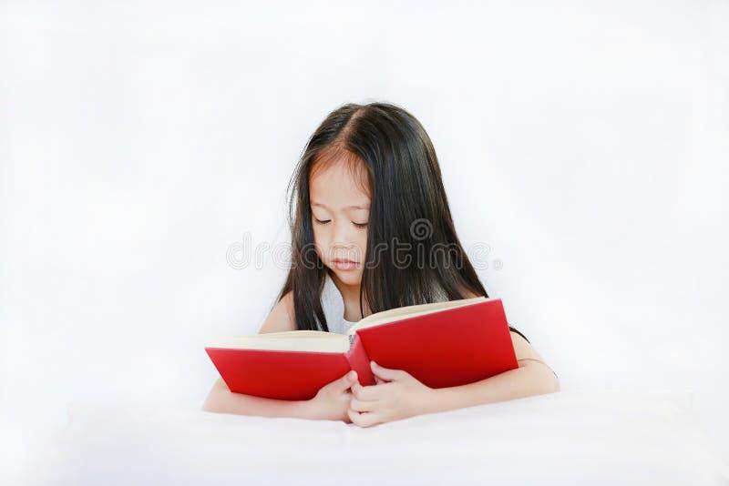 Bello piccolo libro dalla copertina rigida asiatico della lettura della ragazza del bambino che si trova con il cuscino su fondo  fotografia stock libera da diritti