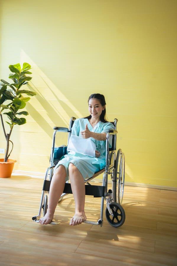 Bello pollice asiatico di rappresentazione del paziente delle donne su, positivo che pensa, concetto di polizza d'assicurazione immagine stock libera da diritti