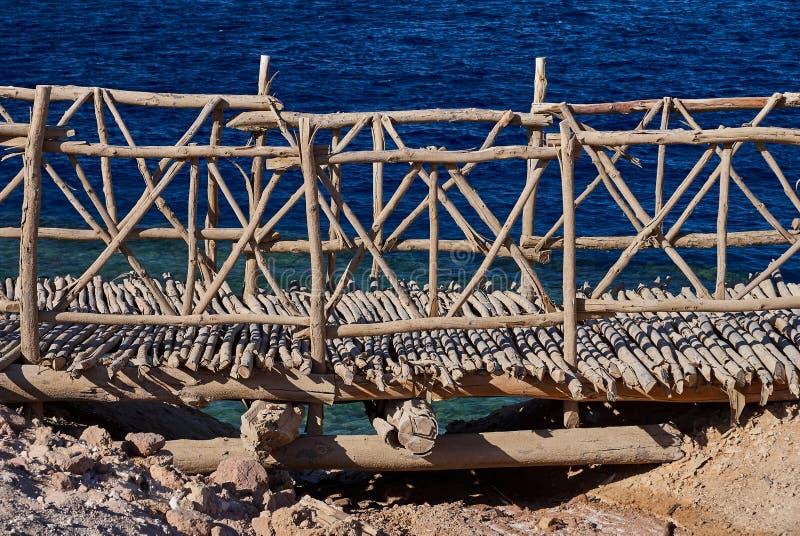 Bello ponte antico di legno decorativo sui precedenti del blu della superficie regolare del Mar Rosso, Sharm el-Sheikh, per esemp immagini stock libere da diritti
