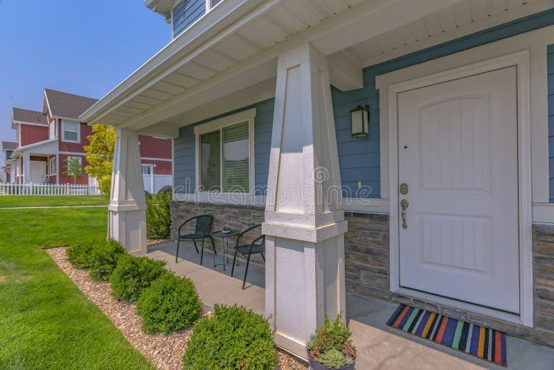 Bello prato inglese e portico anteriore soleggiato di una casa fotografie stock