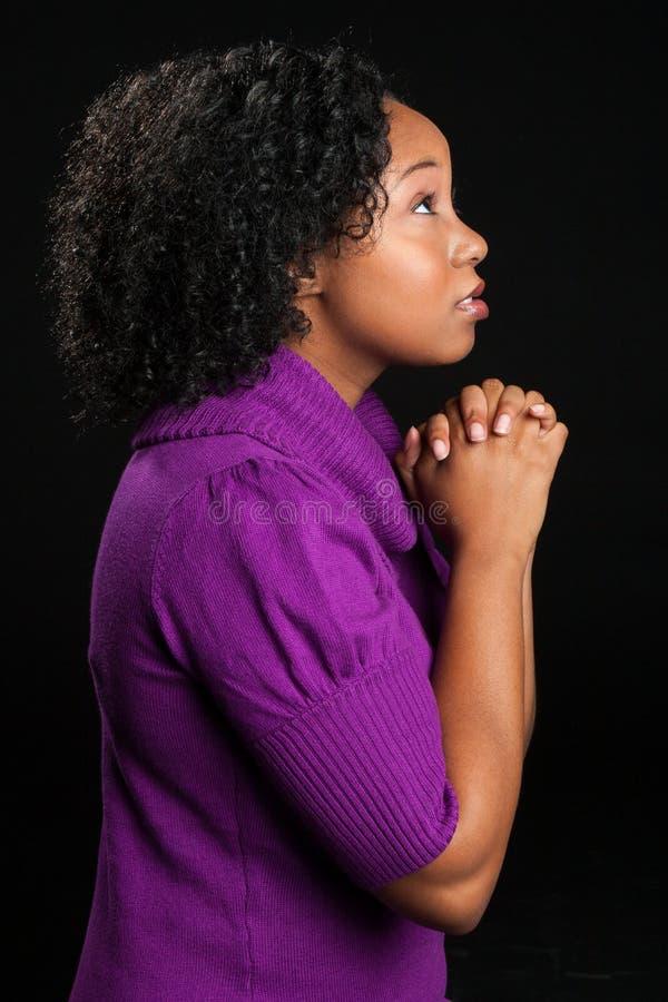 Bello pregare afroamericano della donna immagine stock