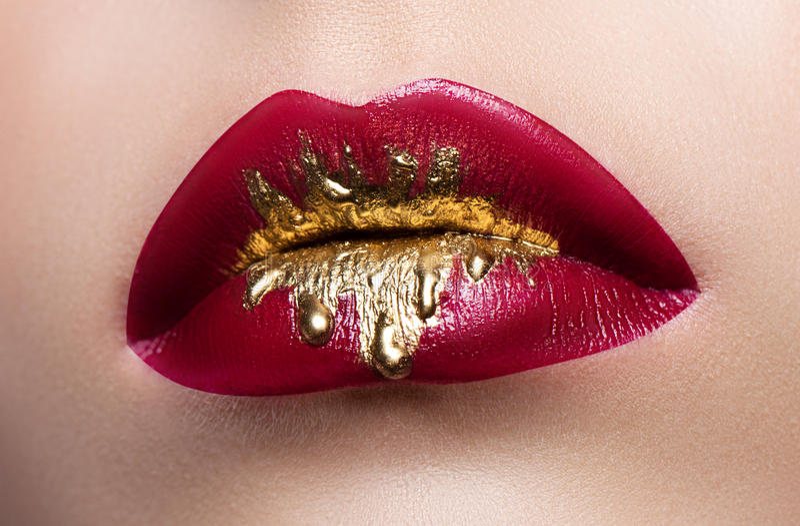 Bello primo piano femminile degli orli Rossetto rosso, pittura dell'oro che circola sulle sue labbra Foto di riserva fotografia stock