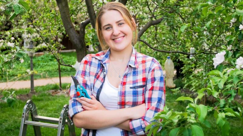 Bello pruner sorridente della tenuta della donna che esamina in camera il frutteto immagini stock libere da diritti