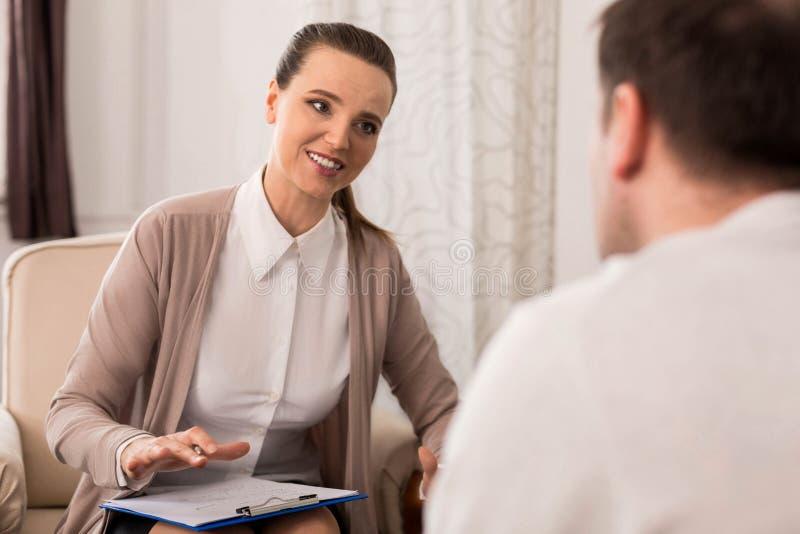 Bello psicologo allegro che lavora con il suo paziente immagini stock libere da diritti