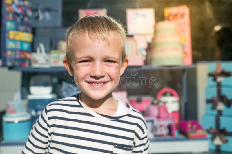 Bello ragazzino felice sveglio che sorride davanti alla stanza frontale di negozio immagine stock