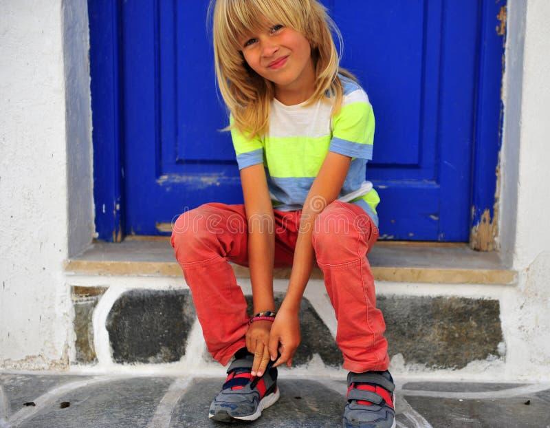Bello ragazzo che si siede sul portico immagini stock