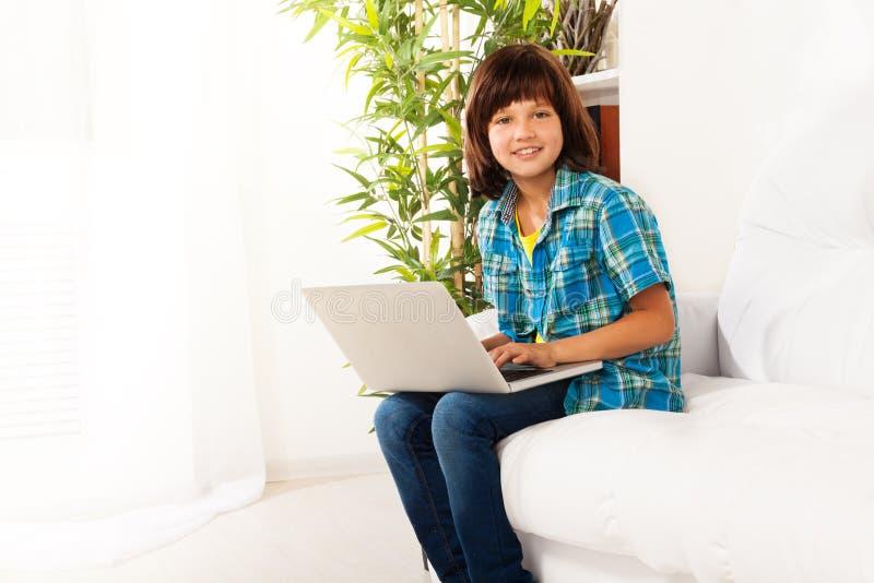 Bello ragazzo con sorridere del computer portatile fotografia stock libera da diritti