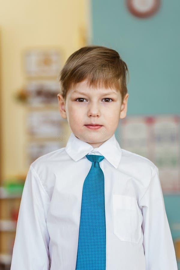 Bello ragazzo di cinque anni in una camicia bianca e un legame del turchese ad una festa nell'asilo fotografia stock libera da diritti