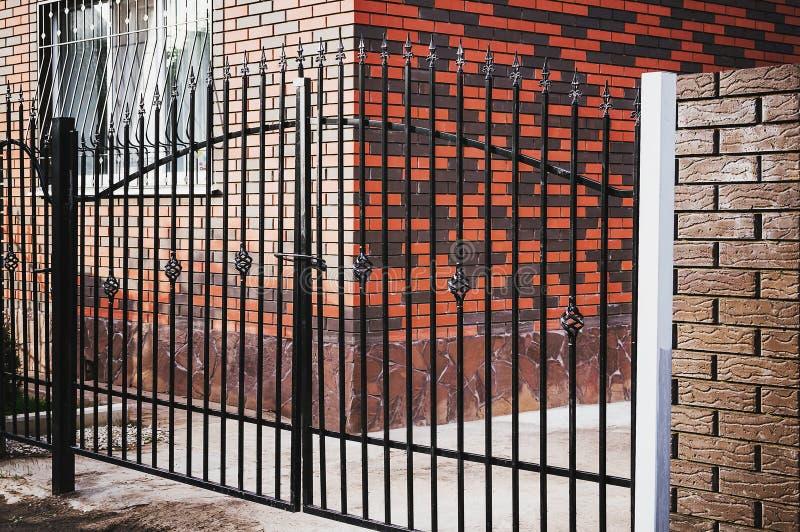 Bello recinto del metallo e del mattone con la porta e portone del recinto moderno Ideas del metallo di progettazione di stile fotografie stock libere da diritti